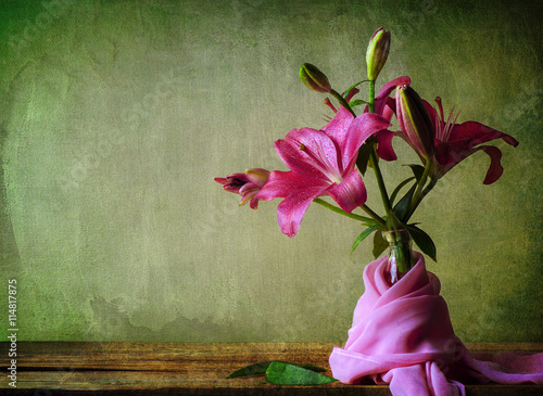 Fotografía  Still life with pink lilies flower and silky scarf on a rustic wooden table