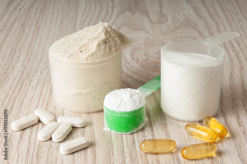 Fotografia  scoop of protein, bcaa and creatine, omega3 in pills