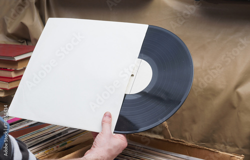 Photo Stands Music store Retro styled image of a collection of old vinyl record lp's with sleeves on a wooden background. Browsing through vinyl records collection. Music background. Copy space.