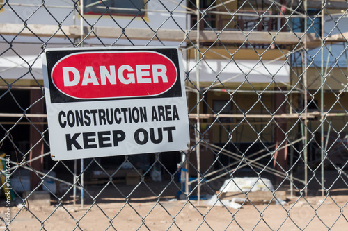 Danger construction area keep out sign in front of building under construction Poster