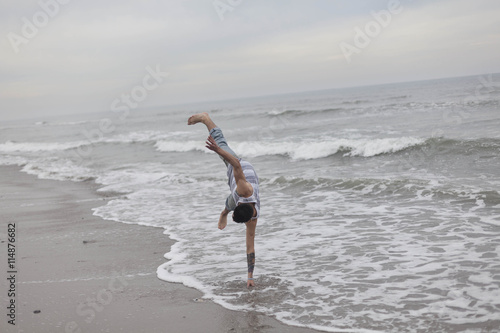 Staande foto Strand Young man doing a handstand on the beach