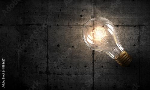 Photo  Light bulb on stone surface . mixed media