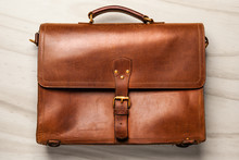 Brown Vintage Leather Briefcase With Strap And Brass Buckle On Wood Background,