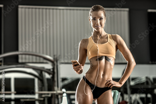 Valokuva  young fitness woman tired in gym and listen music with headset