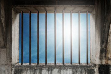 Old window frame with iron bar in jail, and blue sky with bright sunlight