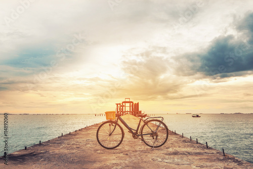 Poster Fiets Vintage bicycle on concrete pier in sunset, vintage tone, soft focus