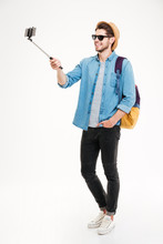 Smiling Young Man Taking Photos With Smartphone And Selfie Stick