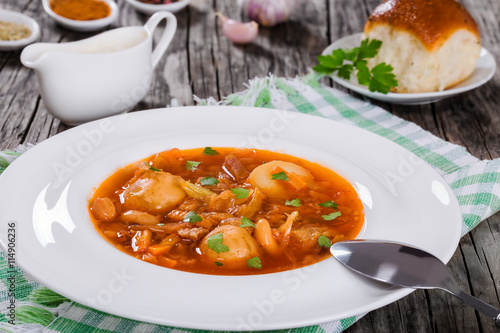 fototapeta na lodówkę Traditional Ukrainian or Russian vegetable soup, borscht cooked in meat broth with new potatoes in white wide rim dish. sour cream in gravy boat and bun sprinkled with garlic on background, close-up