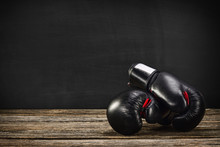 Pair Of Boxing Gloves On A Vintage Wooden Desk With Chalkboard Background. Concept Image, The Idea Of Brutal Competition.