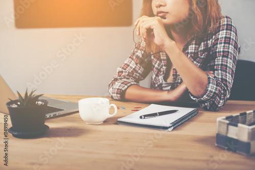 Fotografía  Joven y bella mujer inconformista que se sienta en el lugar de trabajo y el pens