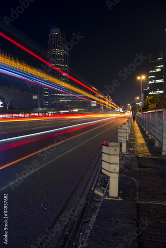 Foto op Aluminium Nacht snelweg Night view of city roads, buildings, skyscrapers, and headlights with light trails