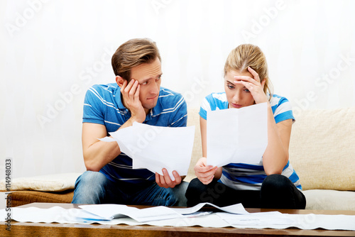 Fotografía  Worried couple after calculating bills sitting at home