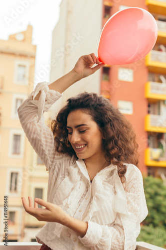 Fotografie, Obraz Young and beautiful woman playing outdoors with a red balloon