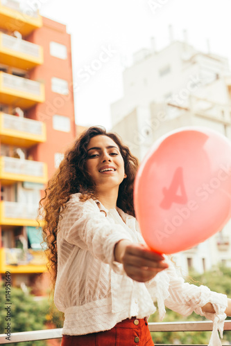 Obraz na plátně Young and beautiful woman playing outdoors with a red balloon
