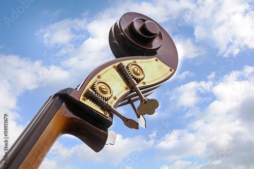 Zdjęcie XXL kontrabas, głowa instrumentu muzycznego na tle błękitnego nieba z chmurami