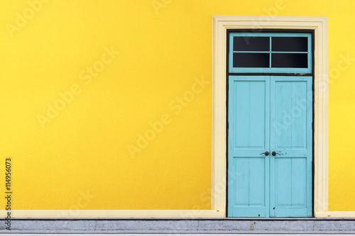Foto op Aluminium Havana Closed blue wooden door on yellow wall background