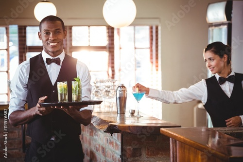 Bartender holding a serving tray with two cocktail glass