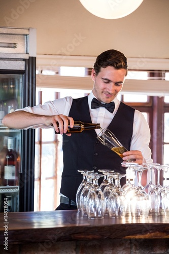 Smiling bartender pouring a beer in a glass Slika na platnu
