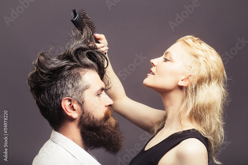 plakat blonde hairdresser combing bearded man