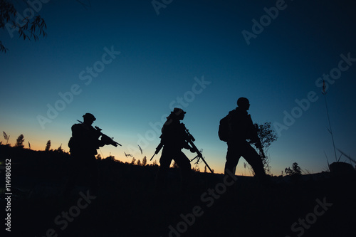 Foto op Canvas Militair Silhouette of military soldiers with weapons at night. shot,