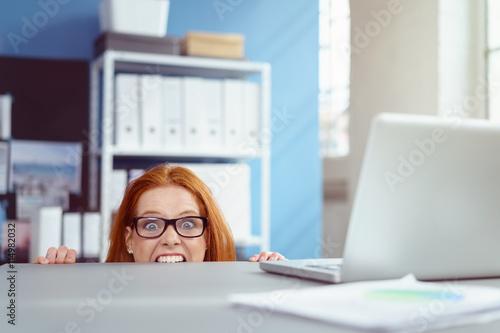Foto genervte frau am arbeitsplatz beißt in die tischkante vor wut