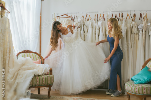 A young bride with her friend choosing wedding dress - Buy this ...