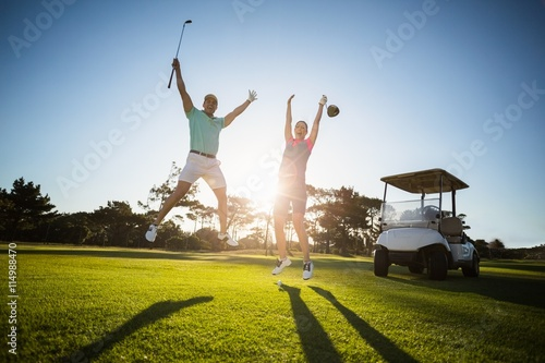 Photo Stands Golf Full length of golf player couple with arms raised