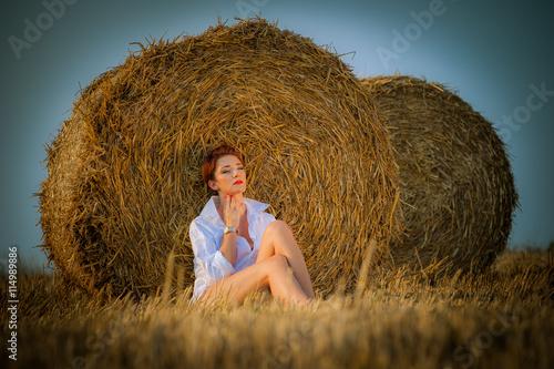 Fototapeta Piękna kobieta na ściernisku ze snopami siana obraz