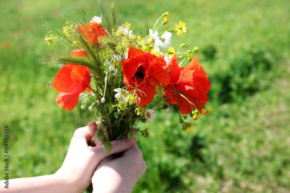 Girl with fresh wildflower bouquet in field