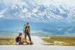 canvas print picture Couple of backpackers wait for a car on the straight road on mountains backdrop