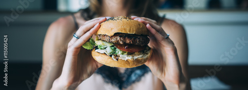 Tablou Canvas Young girl holding in female hands fast food burger, american unhealthy calories