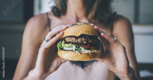 Young girl holding in female hands fast food burger, american unhealthy calories meal on blue background, mockup with space for text message or design, hungry human with grilled hamburger front view