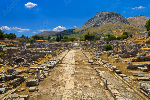 Poster Ruine Greece. The Archaeological Site of Ancient Corinth. Lechaion Road (cardo maximus) paved with limestone slabs and remains of monuments. There is Acrocorinth with fortified citadel in the background