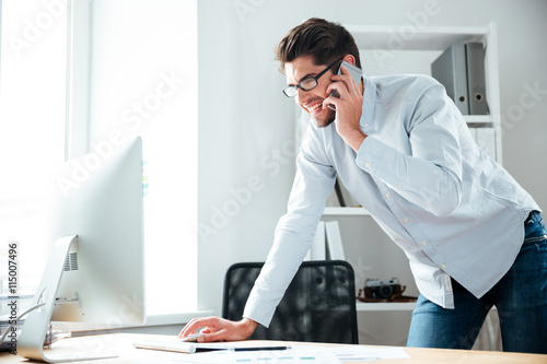 Businessman working with computer and talking on cell phone Poster
