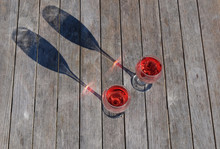 Two Glasses Of Rose Wine Sundowners Casting A Long Evening Shadow On A Wooden Outdoor Picnic Table. Photographed In New Zealand.