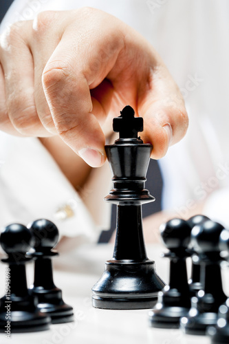 Hand of businessman playing chess Canvas Print