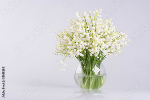 In de dag Lelietje van dalen Lily of the valley in a glass vase isolated on white background