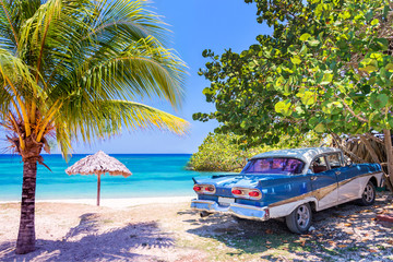 Fototapeta Samochody Vintage american oldtimer car parked on a beach in Cuba