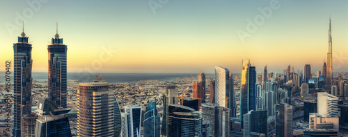 Scenic panoramic view of Dubai modern architecture at sunset. Aerial skyline with downtown skyscrapers.