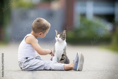 Photographie Enfant parle au chat dans la rue