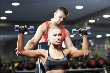 Fototapeta Fitness / Siłownia man and woman with dumbbells in gym