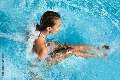 Vászonkép femme avec des jets d'eau dans une piscine