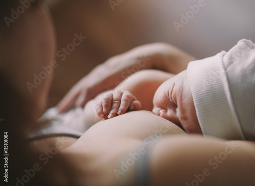 Mother holding her newborn child. Mom nursing baby Poster