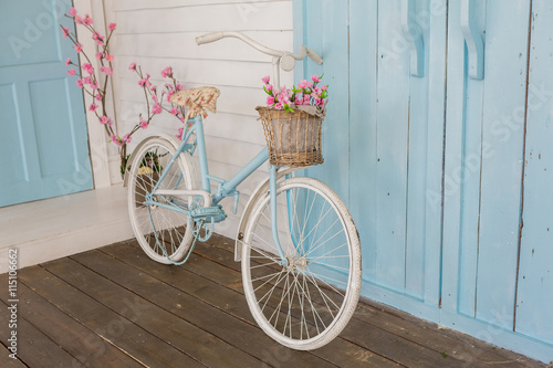 Fotobehang Fiets white and blue vintage bicycle with flowers in a basket