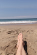 Feet and legs crossed and relaxed on a Southern California beach in the summer with ocean waves in the background.