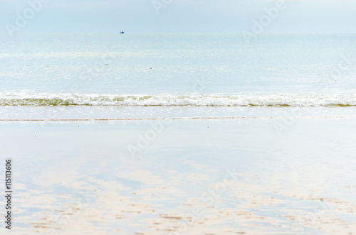 Tuinposter Lichtblauw Landscape view of sea and sand beach with reflection of blue sky