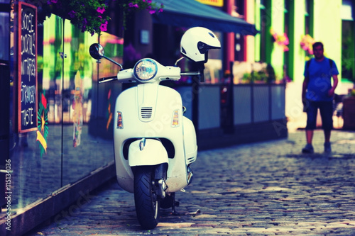 Foto op Canvas Scooter White scooter on the street paving of the old Riga