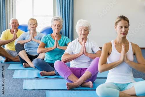Fotografía  Instructor performing yoga with seniors