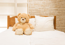 Teddy Bear Toy Sitting Alone On The White Bed
