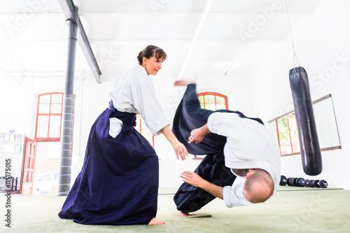 obraz lub plakat Mann und Frau kämpfen bei Aikido Training in Kampfsportschule